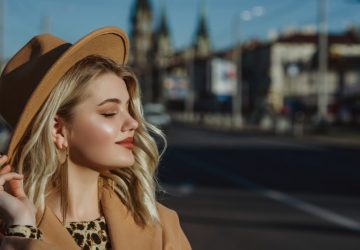 ein Porträt einer attraktiven glücklichen Blondine auf der Straße