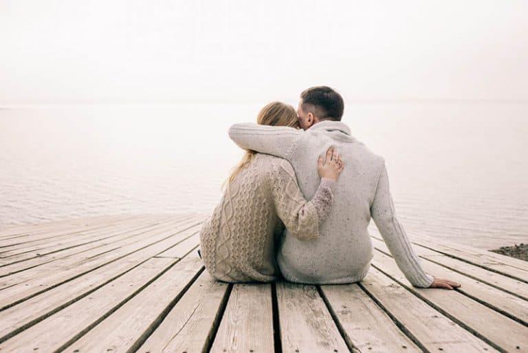 Das umarmende Paar sitzt auf den Brettern am See