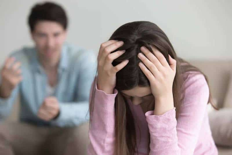 Der Mann schreit die Frau an, die ihren Kopf schützt