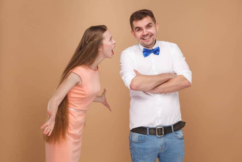 Der lächelnde Mann ignoriert seine wütende Frau
