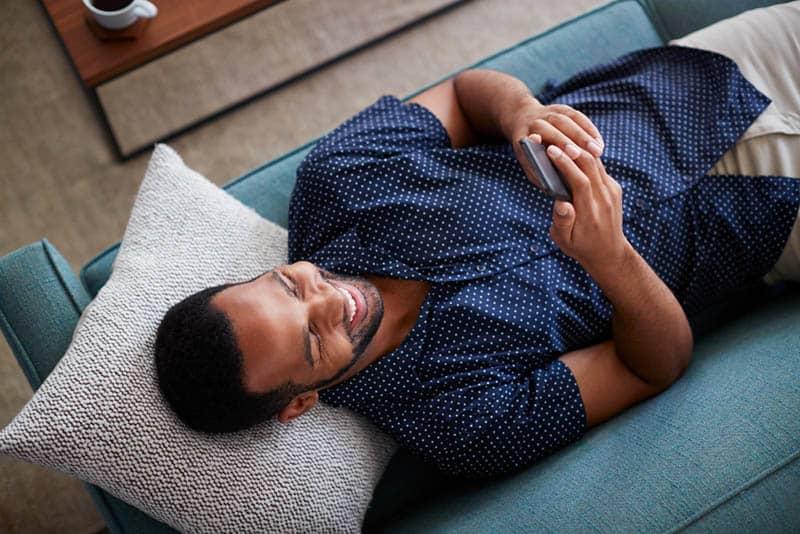 Der schwarze Mann im Hemd liegt auf der Couch und benutzt sein Handy mit einem Lächeln
