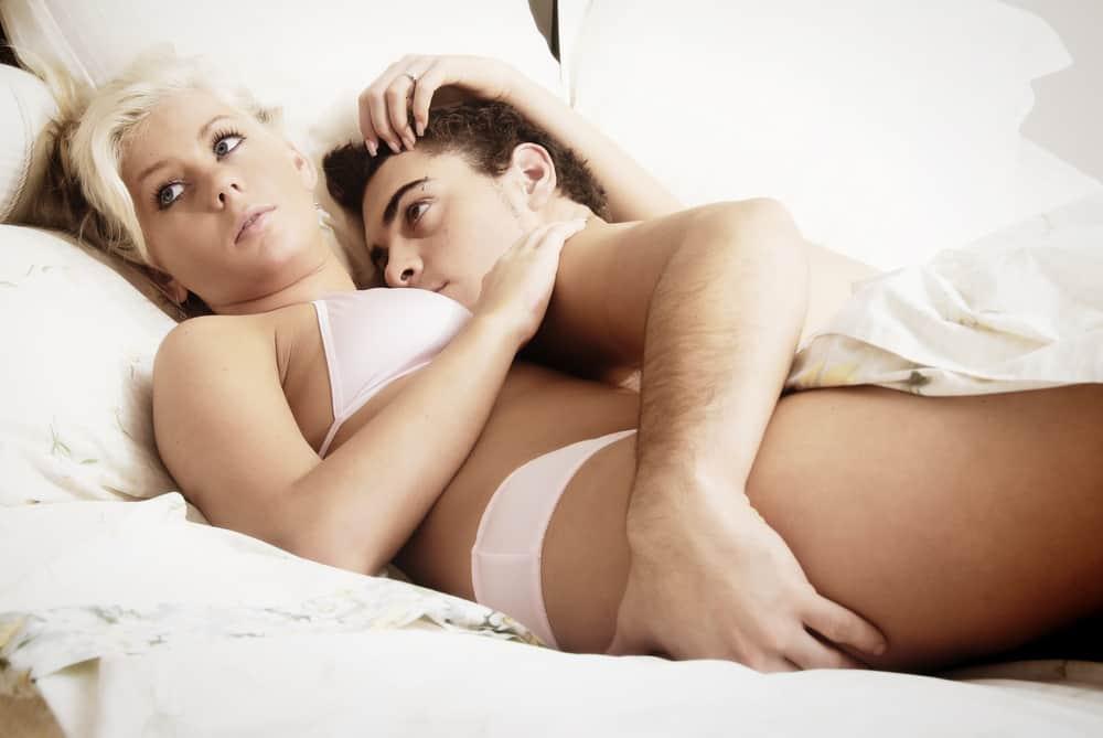 Die Blondine in weißen Dessous liegt mit ihrem Mann im Bett