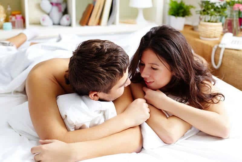 Die Brünette und ihr Mann liegen zufrieden unter einem weißen Laken im Bett