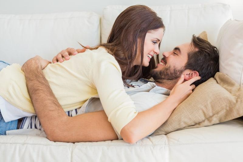 Die Frau liegt auf ihrem lächelnden Mann und sie sehen sich an
