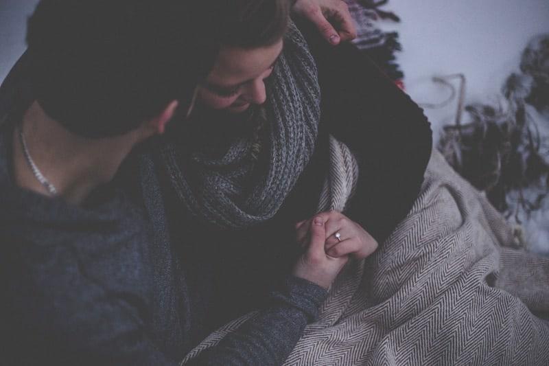 Die Verlobten halten sich an den Händen und sitzen draußen in einer Decke