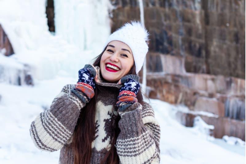 Draußen im Schnee genießt eine lächelnde Brünette