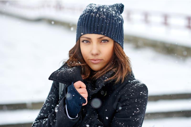 Draußen im Schnee steht eine schöne Brünette