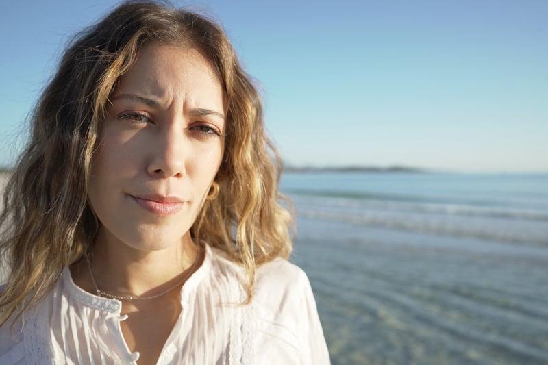 Porträt einer braunhaarigen Frau am Strand