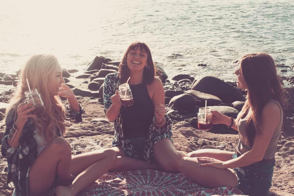 Drei fröhliche Frauen sitzen am Strand und trinken und reden
