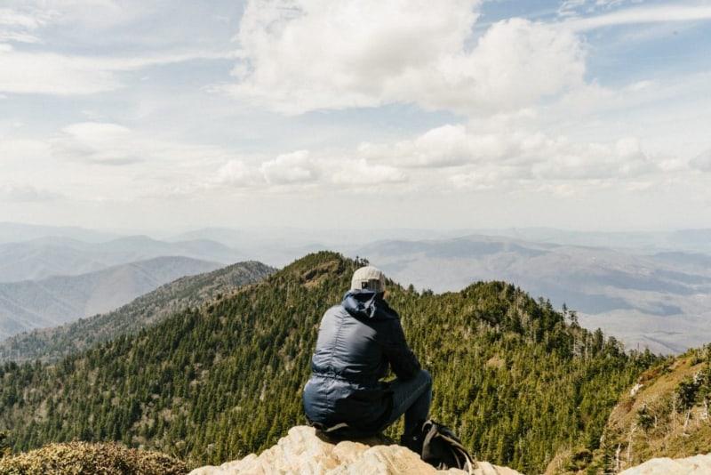 Ein Mann beobachtet den Wald von der Spitze des Hügels(1)
