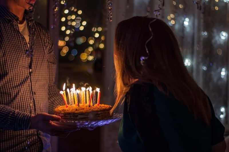 Ein Mann hält eine Geburtstagstorte mit Kerzen für eine Frau