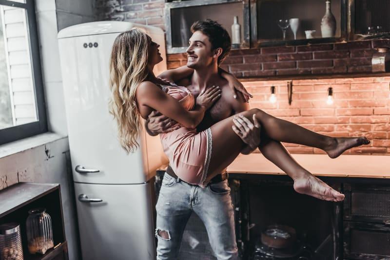 Ein Mann in der Küche trägt eine hübsche Frau in den Armen