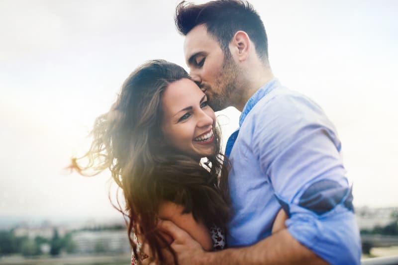 Ein Mann in einem blauen Hemd küsst die Stirn seiner überglücklichen Frau