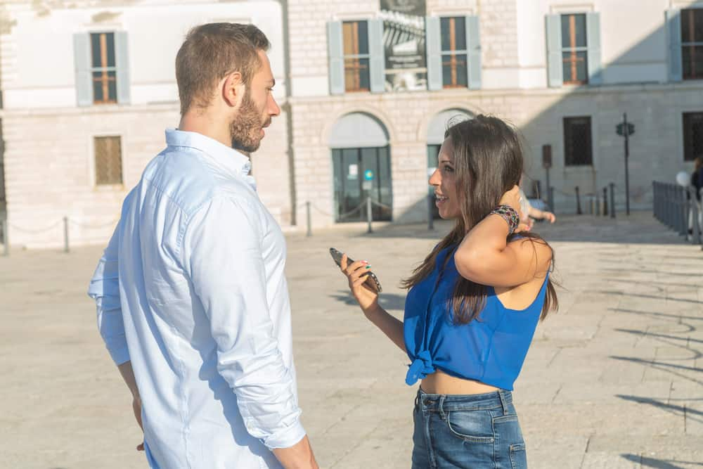 Ein Mann in einem weißen Hemd und eine attraktive Brünette in einem blauen Oberteil sprechen auf der Straße