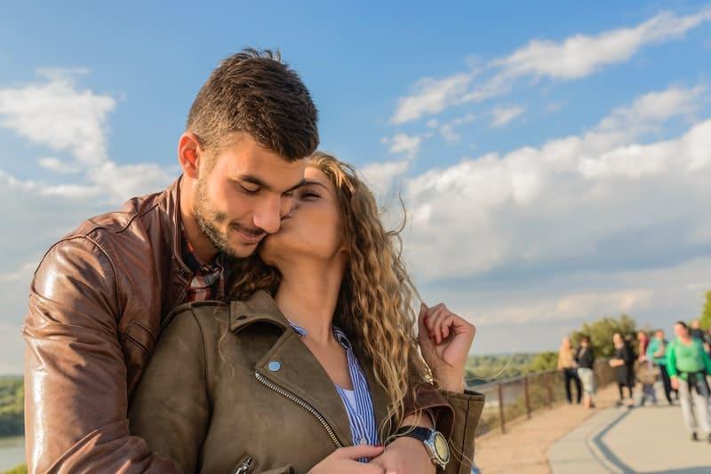 Ein Mann in einer Lederjacke hinter seinem Rücken umarmt seine Frau