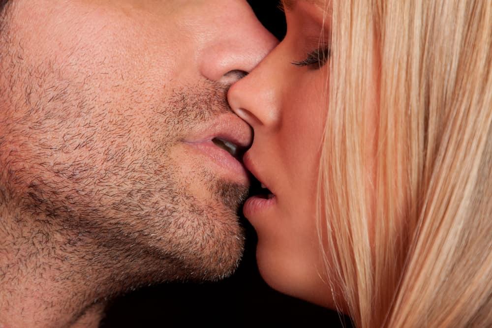 Ein Mann mit Bart küsst seine Blondine