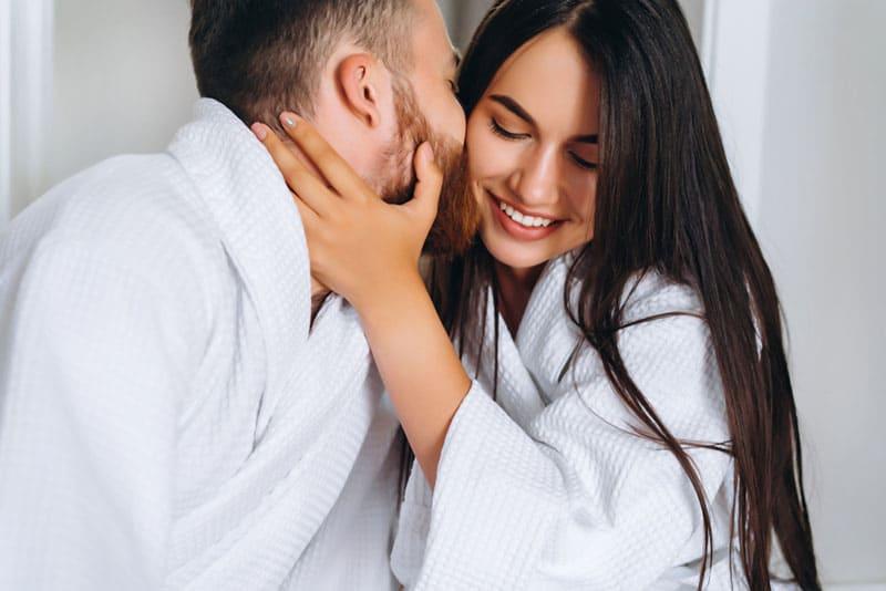 Ein Mann mit Bart küsste seine Frau auf die Wange