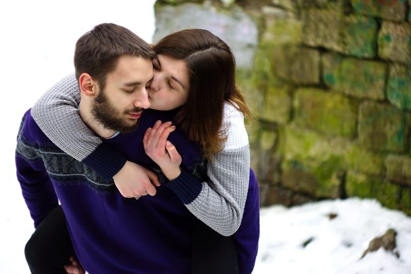 Ein Mann mit Bart trägt eine Frau auf dem Rücken, die ihn küsst