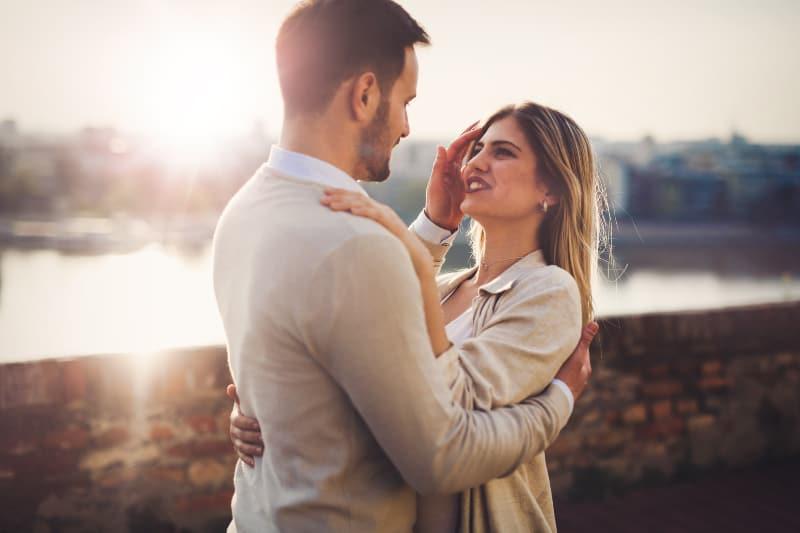 Ein Mann mit Bart und einer glücklichen Frau in einer liebevollen Umarmung über einem Fluss