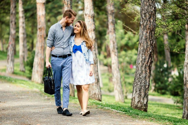 Ein Mann mit Bart und seine Frau in einem Kleid gehen durch den Park