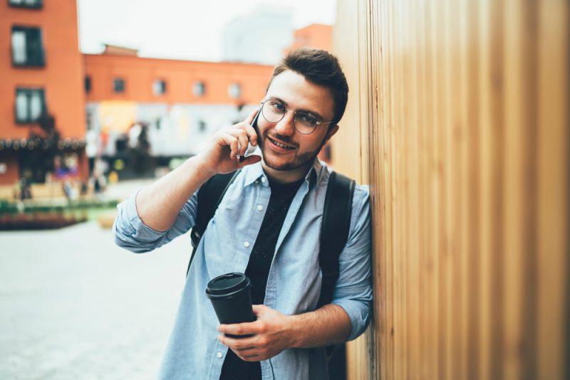 Ein Mann mit Brille spricht auf einem Handy