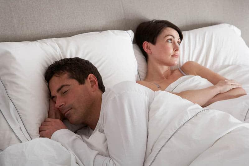 Ein Mann schläft neben einer imaginären Frau