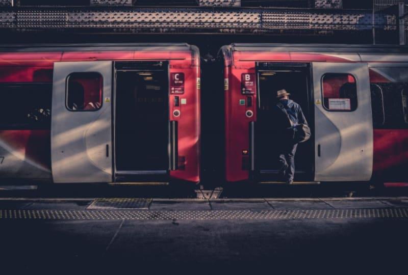 Ein Mann steigt am Bahnhof in einen Zug(1)