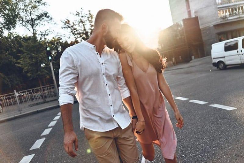 Ein Mann umarmt sanft ein Mädchen, als sie die Straße überqueren(1)