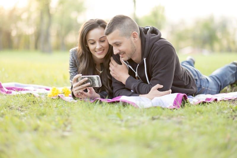 Ein Mann und eine Frau liegen im Park auf einer Decke und schauen sich etwas auf ihrem Handy an