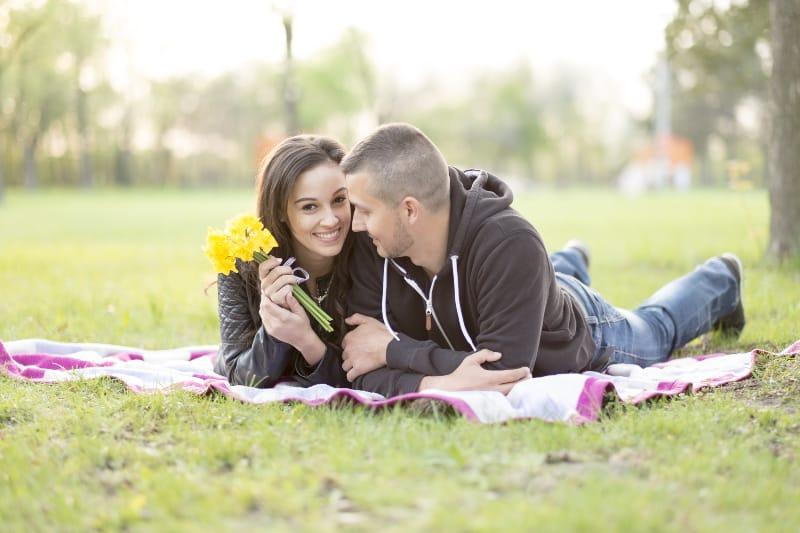 Ein Mann und eine Frau mit Blumen in den Händen liegen auf einer Decke auf dem Rasen