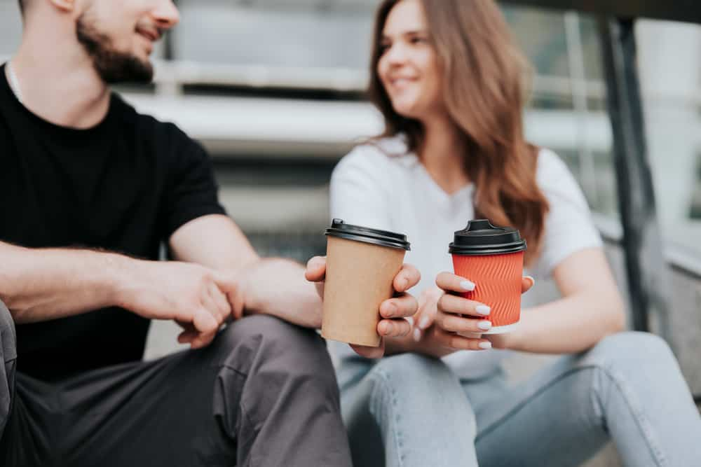 Ein Mann und eine attraktive Frau sitzen draußen und unterhalten sich beim Kaffee