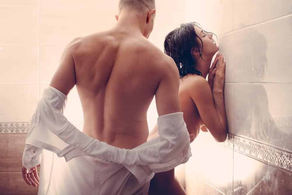 Ein Mann und eine hübsche Frau haben Sex in der Dusche