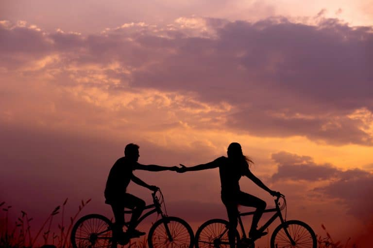 Ein Paar fährt Fahrrad und hält sich an den Händen