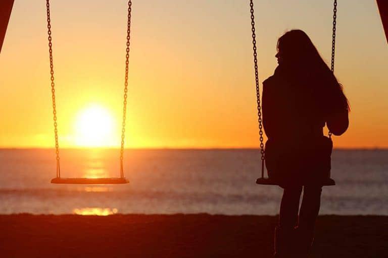 Ein einsames Mädchen schwingt auf einer Schaukel