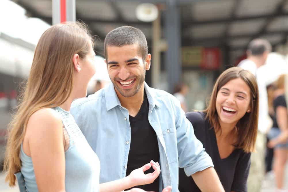 Ein lächelnder Mann und zwei Frauen unterhalten sich