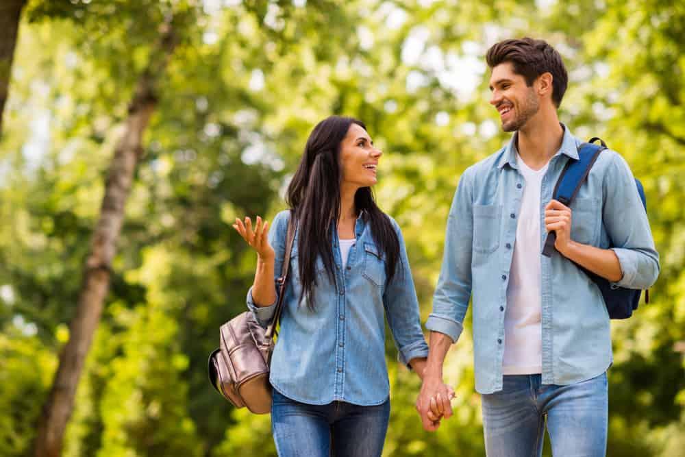 Ein lächelndes Liebespaar geht durch den Park und redet