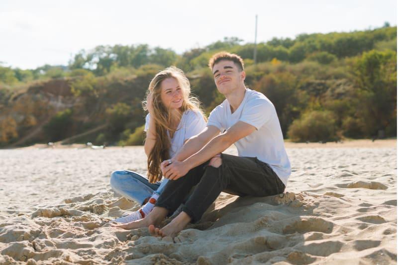 Ein lächelndes junges Liebespaar sitzt an einem Sandstrand