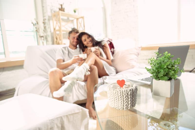 Ein liebevolles Paar in einer Umarmung, das auf einem Zweisitzer sitzt und Kaffee trinkt