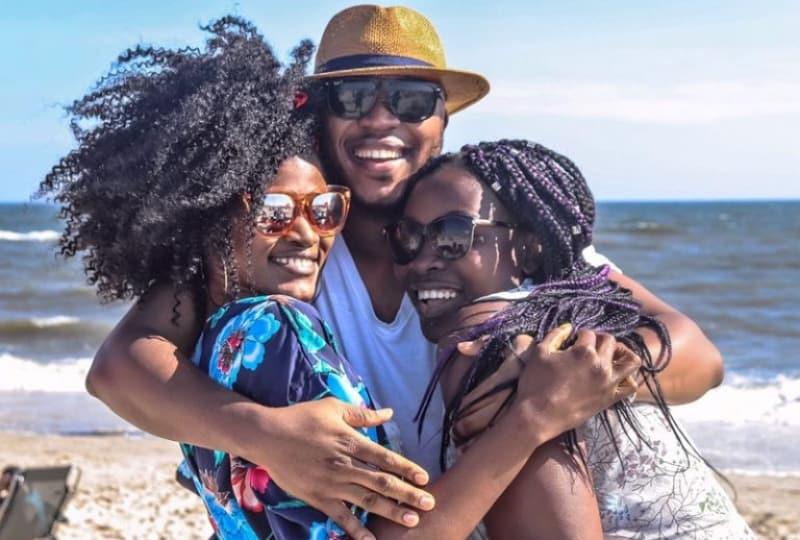 Ein-schwarzer-Mann-am-Strand-umarmt-zwei-schwarze-Frauen
