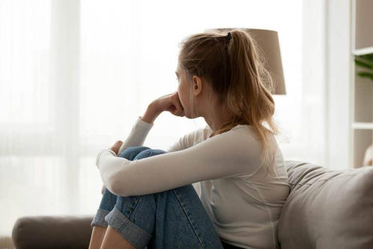 Ein trauriges Mädchen sitzt auf der Couch