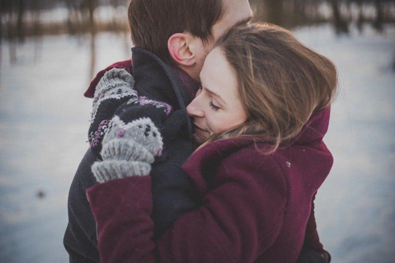 Ein umarmtes Paar steht in den Mänteln im Schnee