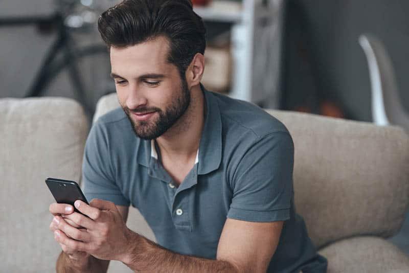 Ein zufriedener Mann sitzt auf der Couch und schreibt auf sein Handy