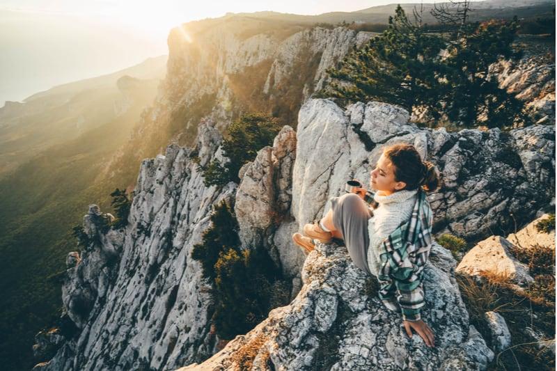 Eine Frau auf einem Felsen sitzt und trinkt Kaffee