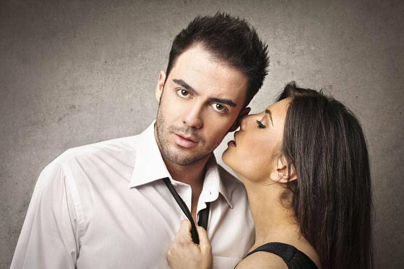 Eine Frau flüstert einem besorgten Mann etwas ins Ohr