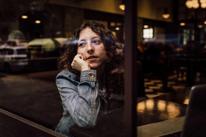 Eine Frau in Jeansjacke sitzt alleine in einem Café am Fenster