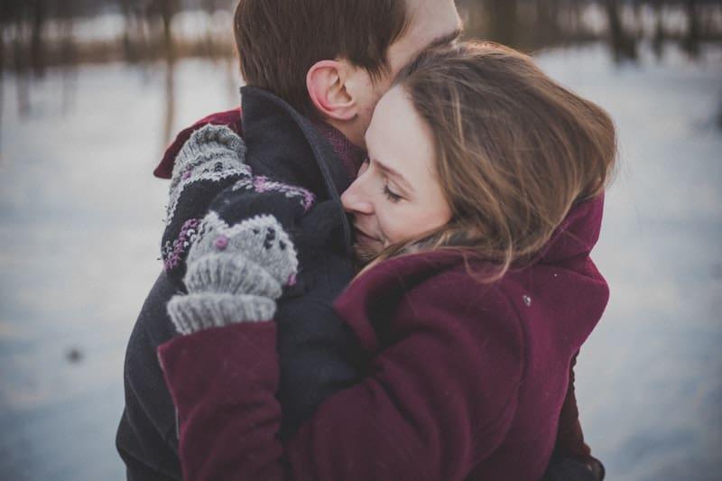 Eine Frau in Wollhandschuhen steht im Schnee und umarmt ihren Mann