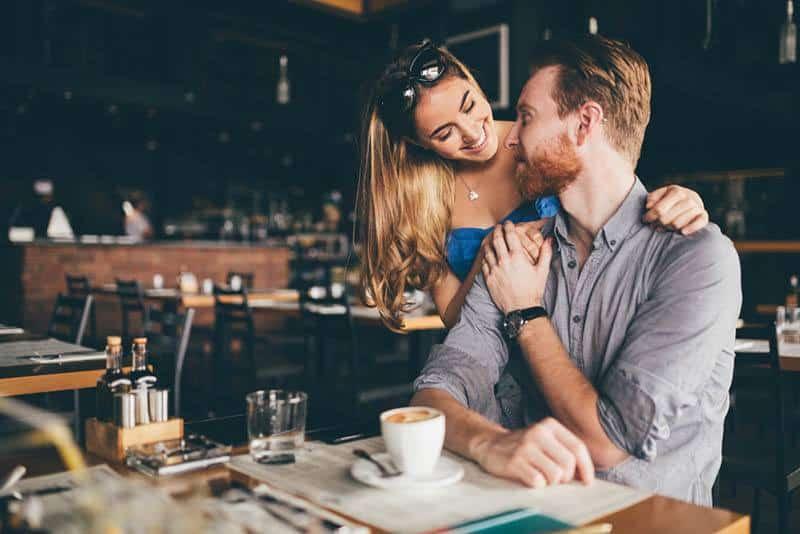 Eine Frau in einem Café umarmt einen Mann hinter ihrem Rücken