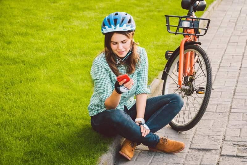 Eine Frau sitzt auf dem Bürgersteig und schreibt eine Nachricht auf ihr Handy