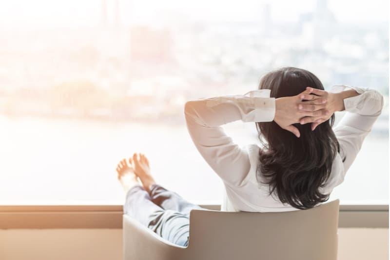 Eine Frau sitzt in einem Sessel auf der Terrasse und ruht sich aus