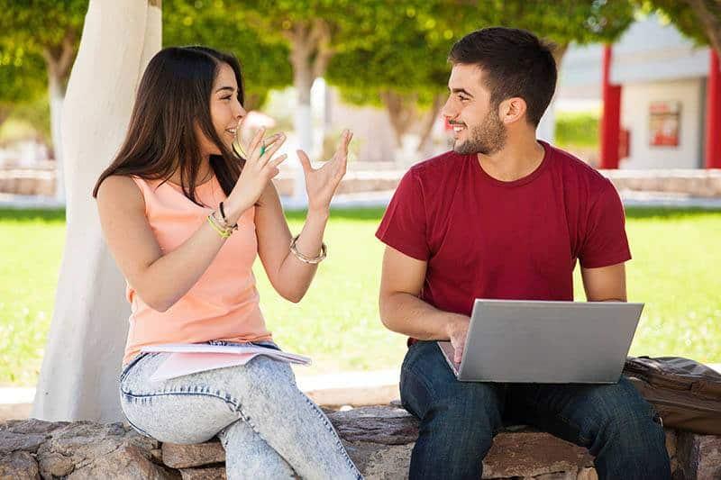 Eine Frau und ein Mann sitzen draußen auf einer Steinmauer und unterhalten sich